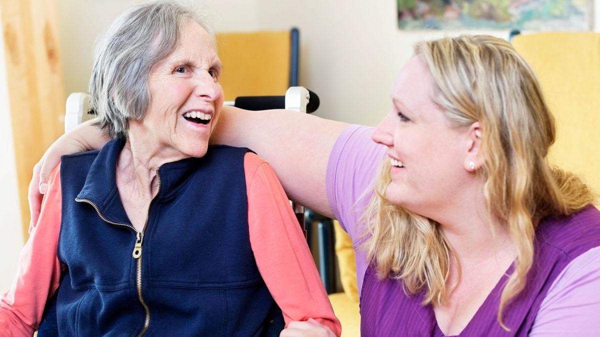 Äldre kvinna och personal skrattar och har trevligt.