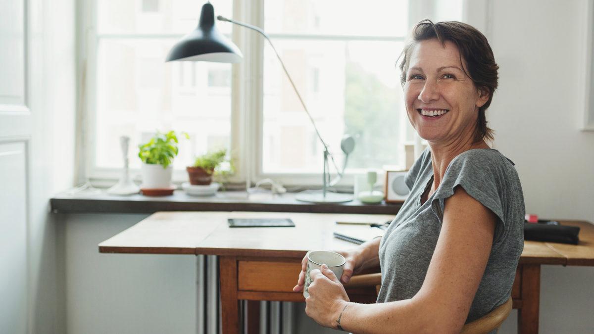 Kvinna vid arbetsbord hemma framför fönster.