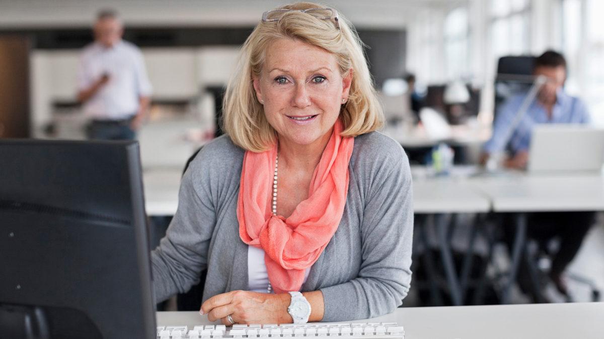 Kvinna vid dator i öppet kontorslandskap