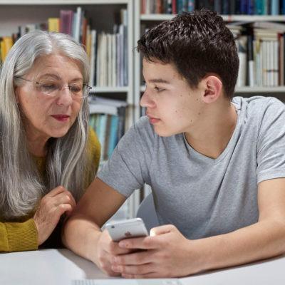 Äldre kvinna och ung pojke samtalar vid ett bord framför en bokhylla.