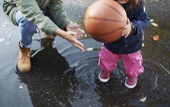 Förskolepersonal i vattenpöl hjälper barn med boll
