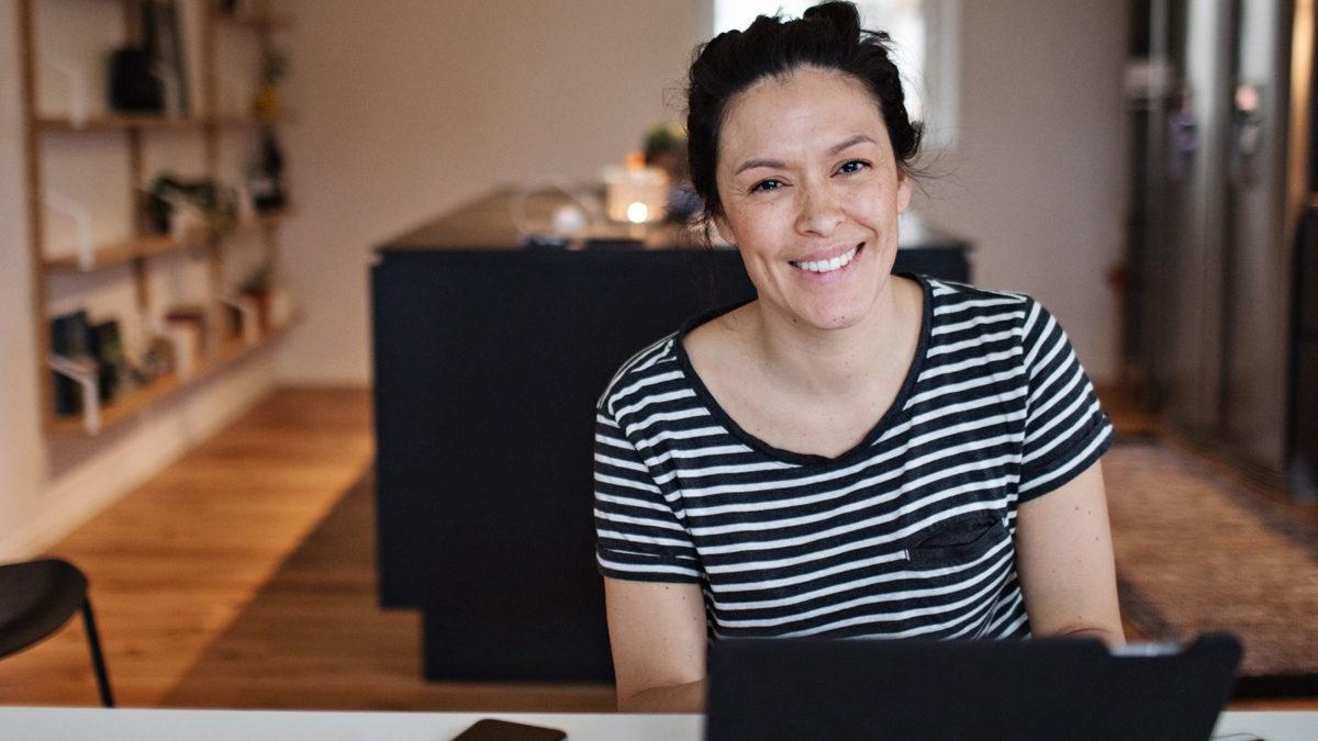 Leende kvinna vid datorskärm i hemmiljö.