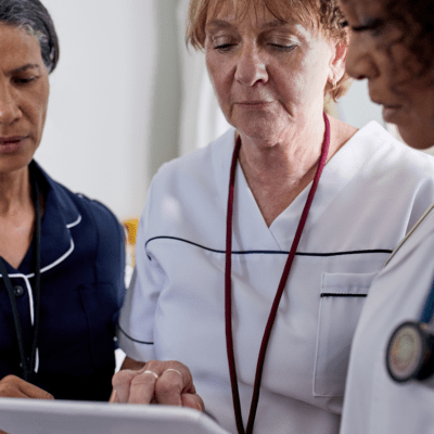 Tre kvinnor i sjukhuskläder diskuterar
