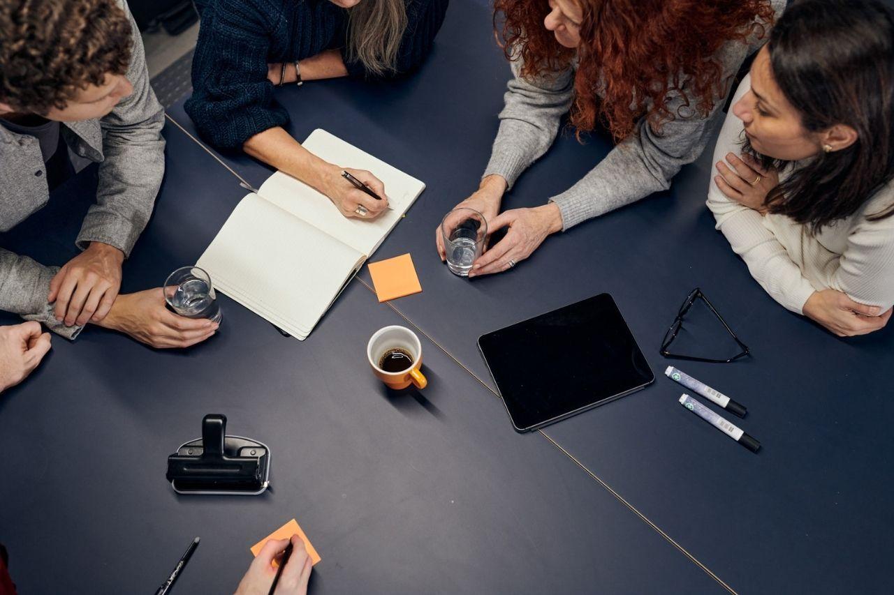 Flera kollegor sitter och jobbar tillsammans runt ett bord. En antecknar i ett block.