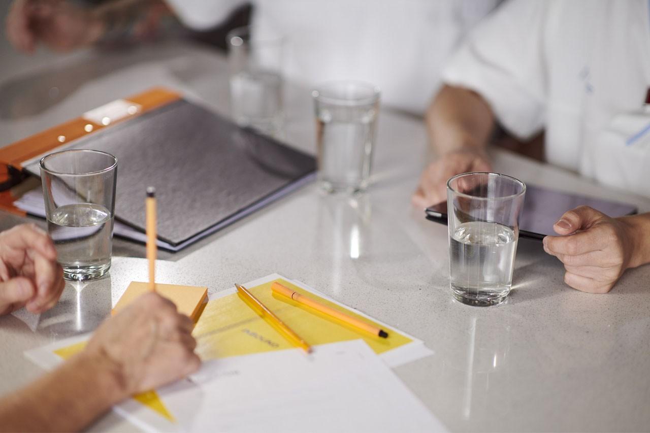 Kollegor runt ett bord med en pärm, papper, pennor, notislappar en läsplatta.