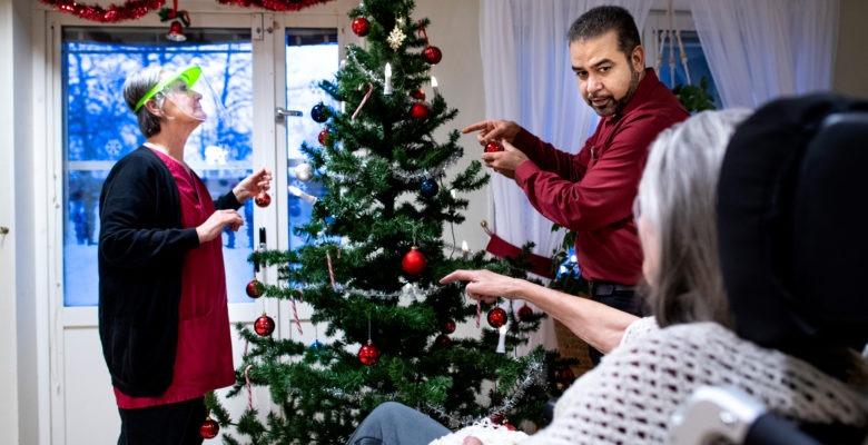 Två personer ur personalen klär julgranen medan en boende tittar på och pekar
