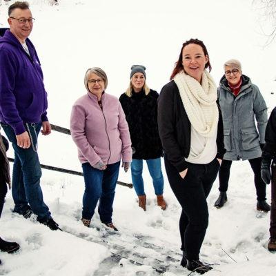 Sju personer från Lyckseles samverkansgrupp står utomhus i en snöig trappa.