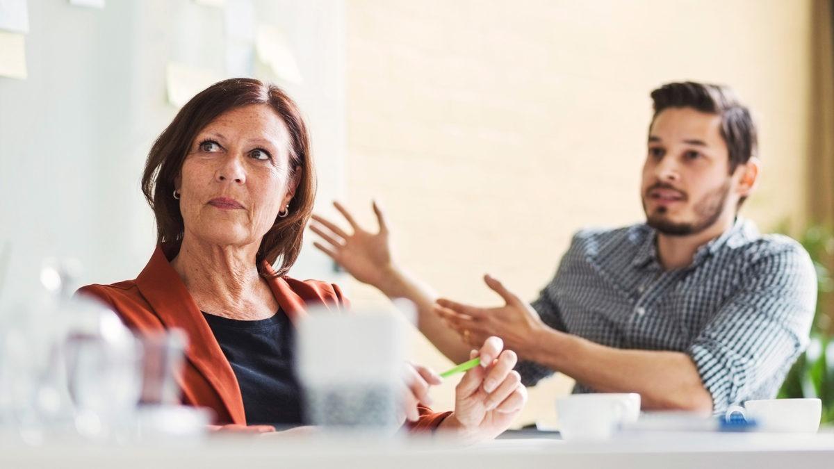 En kvinna som lyssnar och en man som pratar engagerat vid ett bord.