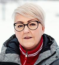 Erika Hasselvik med snö bakom. Hon har kort hår och grå jacka.
