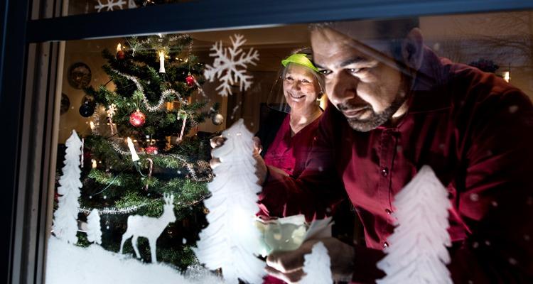 Två personer ur personalen pyntar ett fönster på ett äldreboende