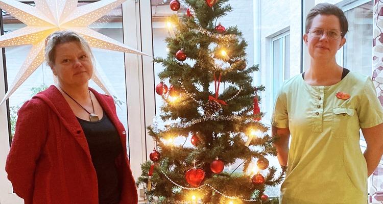 Maggan Östlund och Camilla Spång står framför en julgran