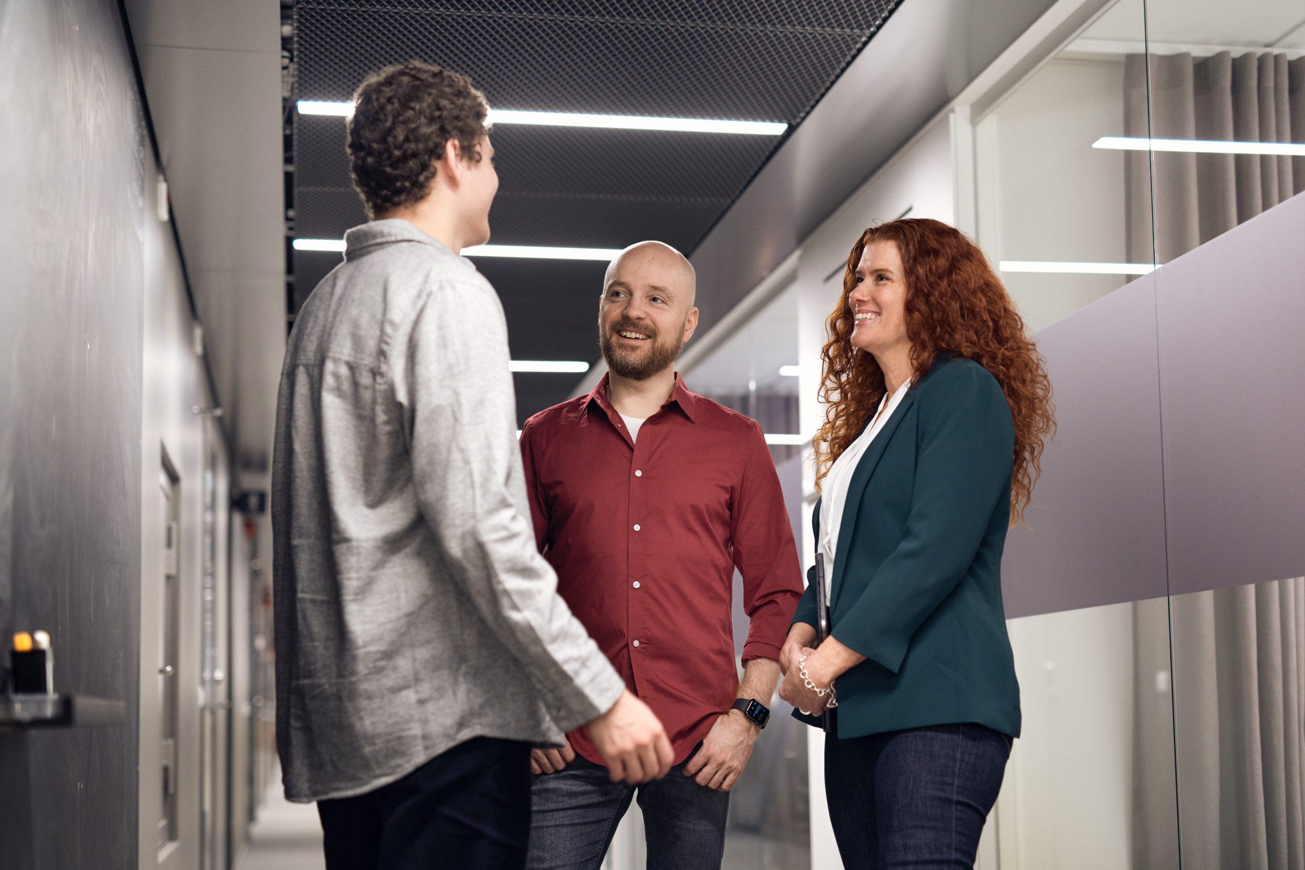 Tre kollegor pratar utanför ett mötesrum.