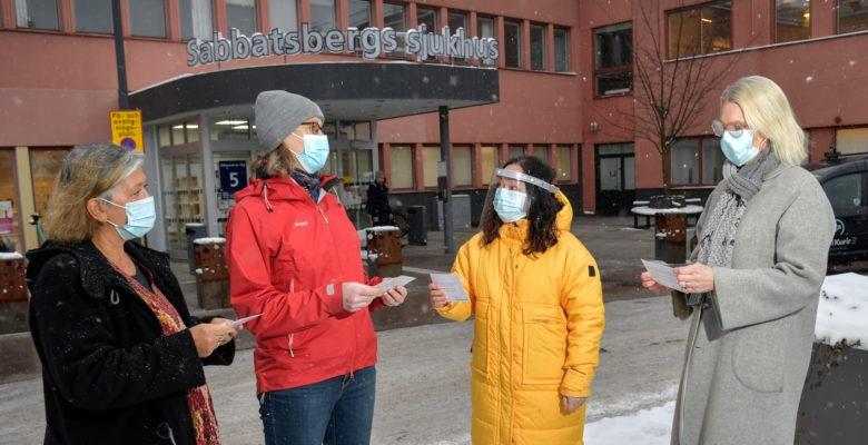 Chefer och skyddsombud håller i reflektionskort utanför entrén till Sabbatsbergs sjukhus