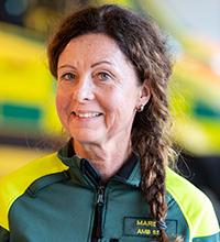 Skyddsombudet Marie Johansson framför ambulansen.