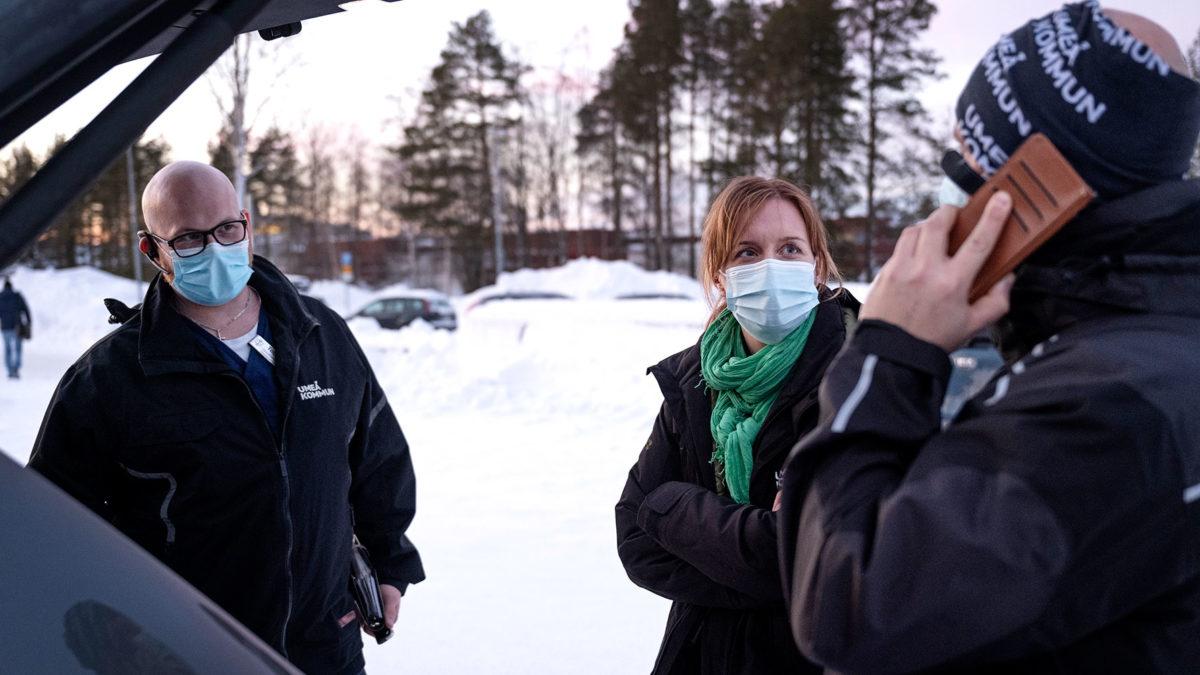Tobias Ångqvist, Ingela Lundström och Dennis Kallin i samtal vid en öppen baklucka på en bil.