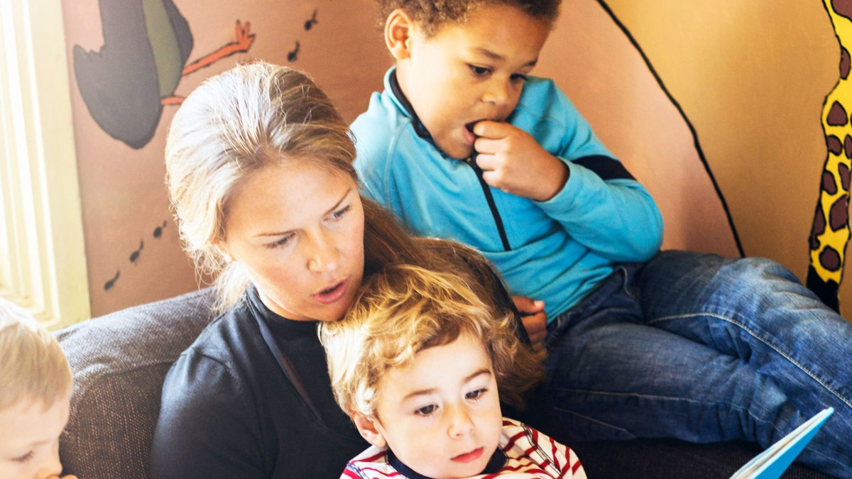 Kvinna som arbetar i förskola läser högt ur bok för flera barn.