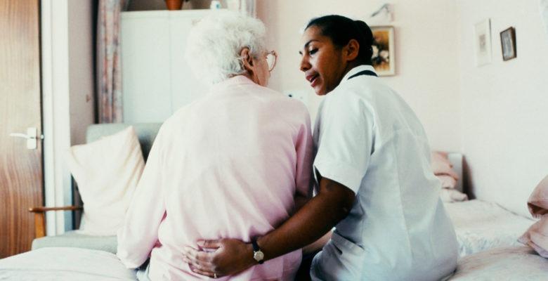 En äldre dam och en sköterska sitter på en säng