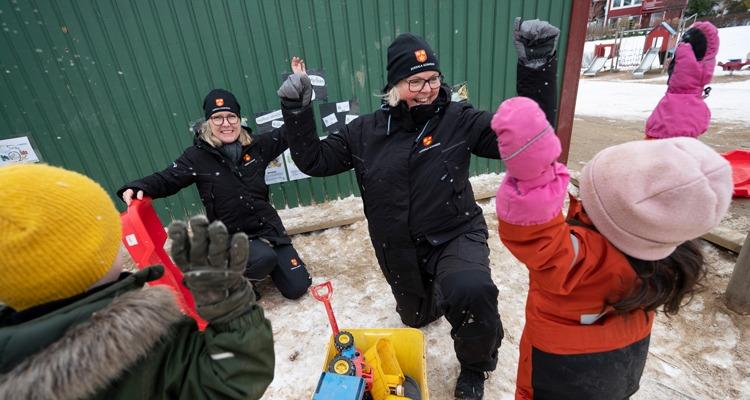 Förskolepersonal och barn på förskolegården