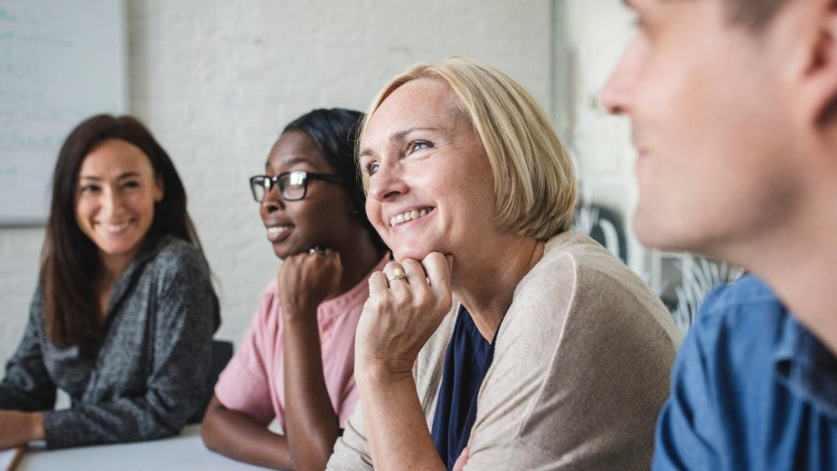 Fyra personer i ett mötesrum kommunicerar, lyssnar.