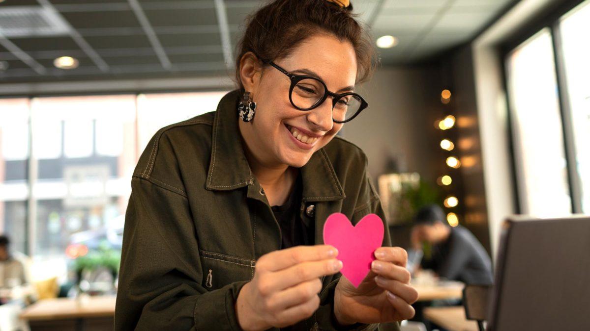 Kvinna håller upp ett rött hjärta framför en datorskärm.