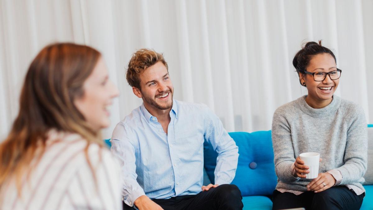 Tre kollegor vid ett kaffebord ser glada ut