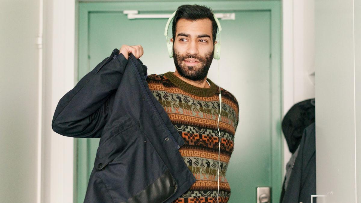 En person med hörlurar på tar på sig en jacka