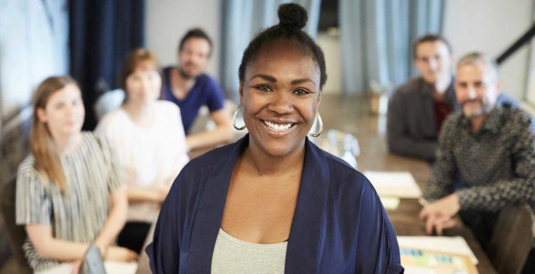 Kvinna som står framför arbetskamrater som sitter runt ett bord.