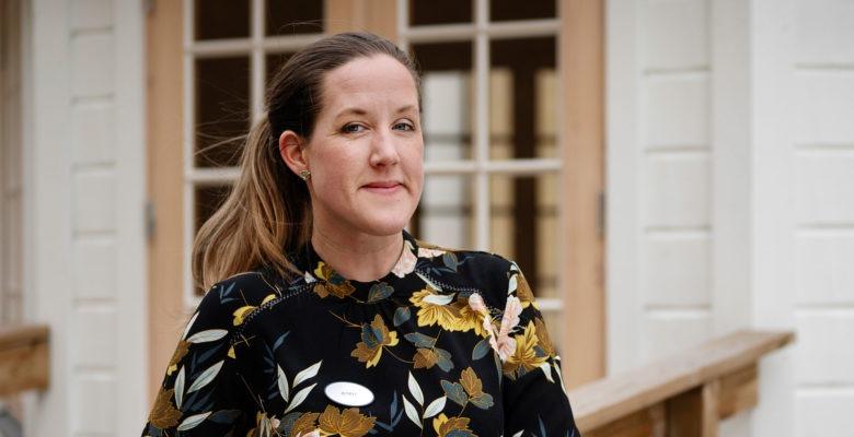Jenny Häggström lutar sig mot ett räcke utanför sin arbetsplats.