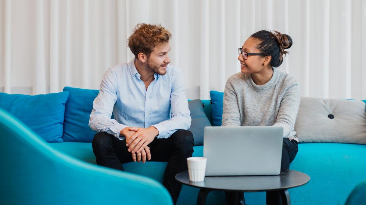 Två personer i en soffa pratar med varandra