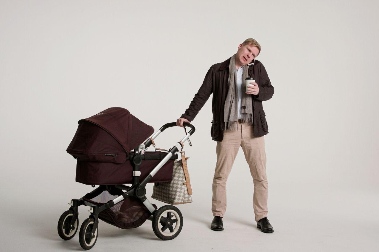 Man med barnvagn och kaffekopp i handen pratar i mobilen.
