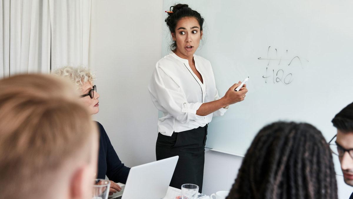 Kvinna som skriver på tavla och tittar mycket förvånat på fyra mötesdeltagare när det blev dålig stämning.