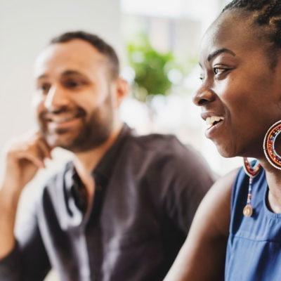 Sittande svart kvinna i profil och en man i bakgrunden.