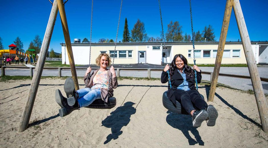 Gunilla Falk och Helena Eriksson gungar på skolgården i Bjurholm.
