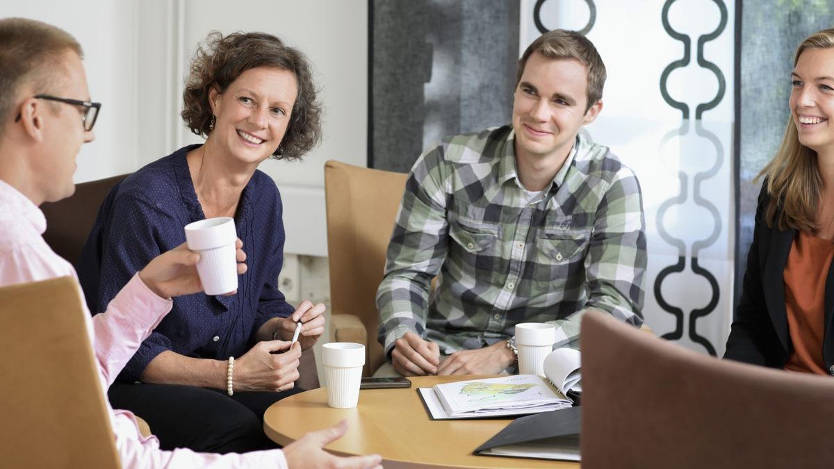 Två män och två kvinnor fikar och ler vid bord, tema inkludering hbtq.
