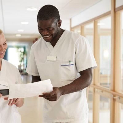 en man med afrikanskt utseende och en blond kvinna, både i arbetskldäer för vården, lutar sig över ett papper och ler, stående i en ljus korridor.