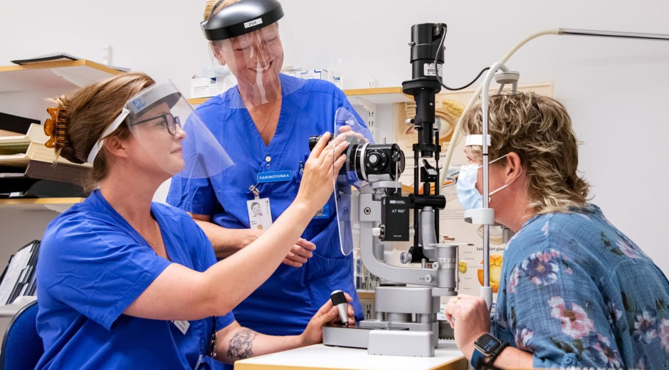 sjuksköterska sitter vid en apparat och tittar en patient i ögat. Intill står en annan sjuksköterska.