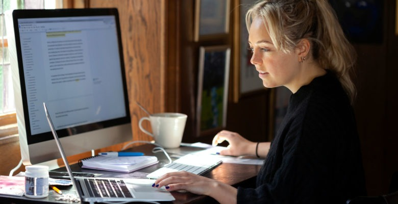 kvinna som arbetar framför två datorskärmar i hemmiljö.