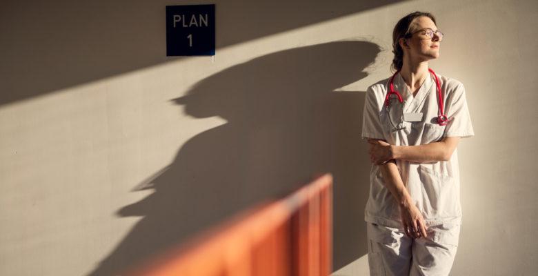 En läkare står och återhämtar sig i en solig trappuppgång