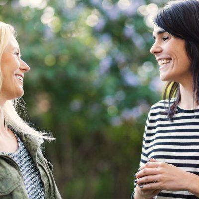 Två glada kvinnor vända mot varandra utomhus.