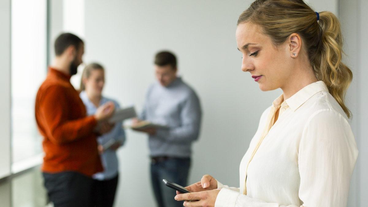 Kollegor på kontor, där kvinna i förgrunden tittar ner i mobil - tema kränkande särbehandling.
