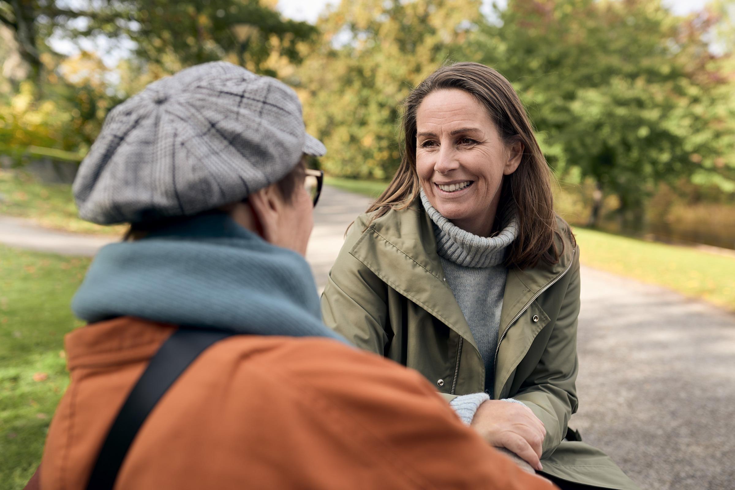 Två kvinnor i samtal på en parkbänk. Den ena kvinnan ler mot den andra.