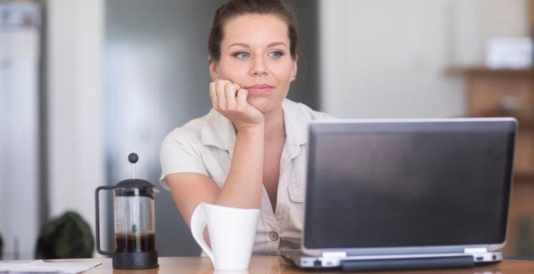 En kvinna sitter vid en laptop och ser avslappnad ut