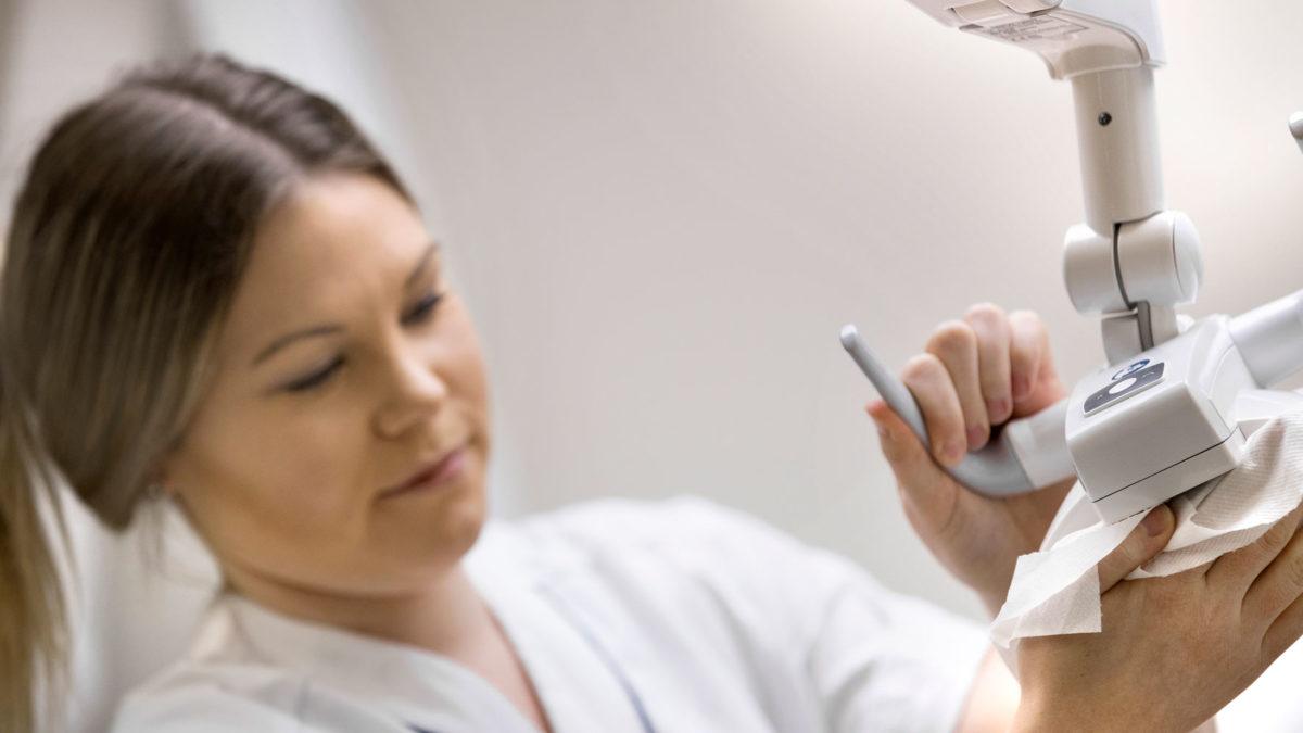 Elin Broling, en ung tandsköterska, torkar av en undersökningslampa i ett undersökningsrum för tandvård.