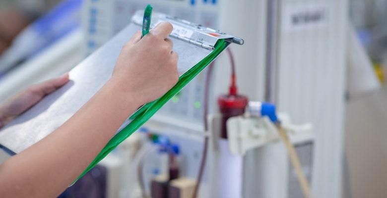 en hand skriver något på ett skrivblock. I bakgrunden en dialysapparat och skymten av en patient.