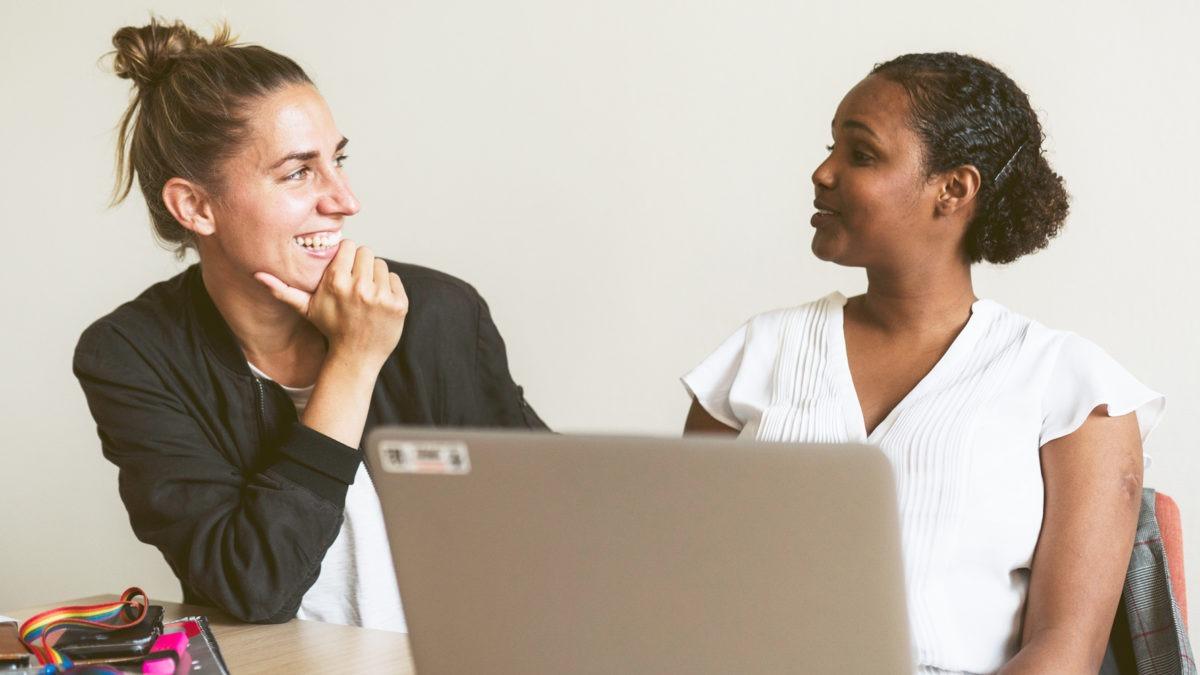 två kvinnor visd en dator som tittar på varandra och ler.