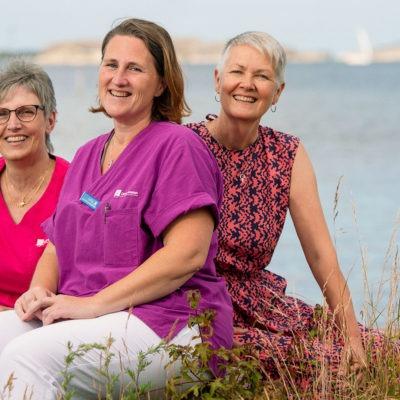 Tre glada kvinmnor sitter tätt ihop på en gräskull, med havet i solljus bakom sig.