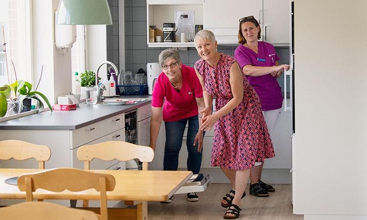 tre leende kvinnor i ett kök på ett äldreboende, i färd med att ploca ur diskmaskinen och öppna kylskåpsdörren.