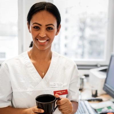 ung kvinnlig läkare med kaffekopp i ghanden i ljust rum med skrivbord och dator bakom sig.