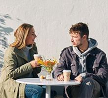 två personer sitter och fikar utomhus i solen, med jackorna på.