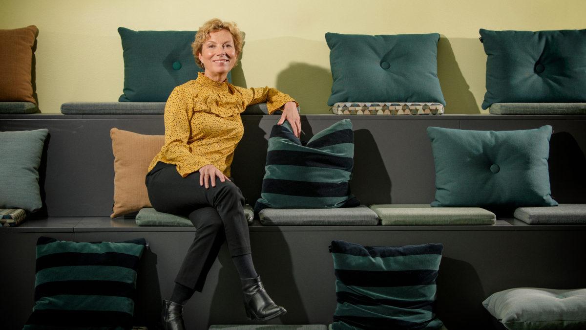 Pia Kragh Jensen sitter i en i övrigt tom sittplats-trappa med kuddar.